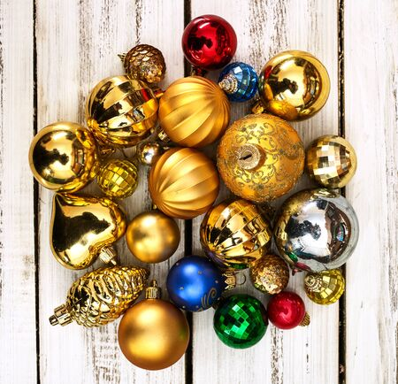 Christmas wreath of Xmas balls decorations hangs on front door who made from white wooden boards on square frame.