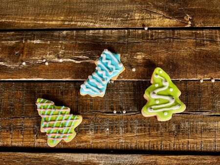 Decorative Christmas cookies sparse on wooden board background. Top view of three ginger biscuits Xmas tree with icing on square frame.