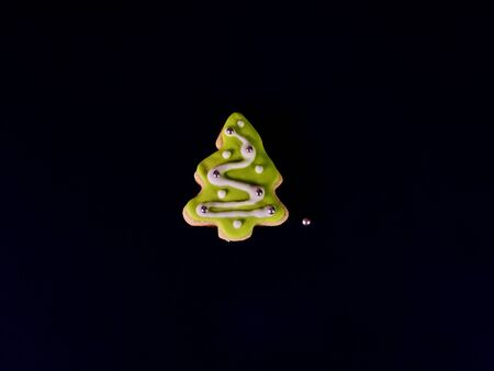 Decorative Christmas cookies. Ginger biscuits Xmas tree with icing on black background.