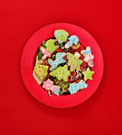 Christmas gingerbread cookies on red Xmas plate and same color background . Top view long vertical design frame with copy space top.