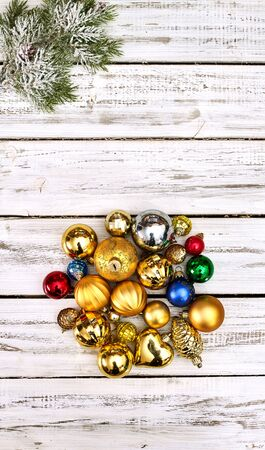 Christmas wreath of Xmas balls decorations hangs on front door who made from white wooden boards.