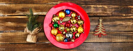 Christmas decorations design of Xmas balls ornaments on red plate with green tree on wooden boards. Horizontal long frame banner.