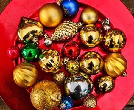 Christmas decorations design top view of Xmas balls ornaments on close up red plate.