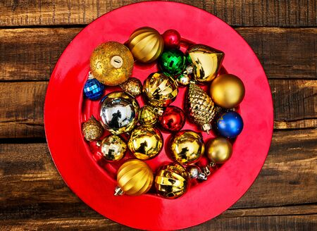 Christmas decorations design top view of Xmas balls ornaments on red plate on wooden boards .