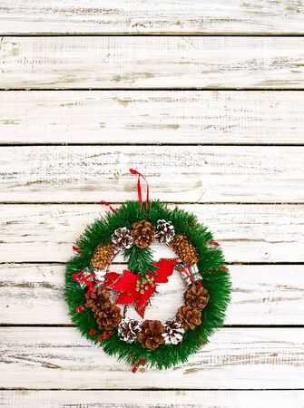 Christmas wreath with winter red flower in middle decoration hangs on white front door. Vertical frame with copy space top.