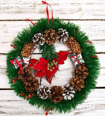 Christmas wreath with winter red flower in middle decoration hangs on white front door. Square frame.