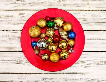 Christmas decorations design top view of Xmas balls ornaments on red plate onto horizontal white wooden boards . Standard-Bild