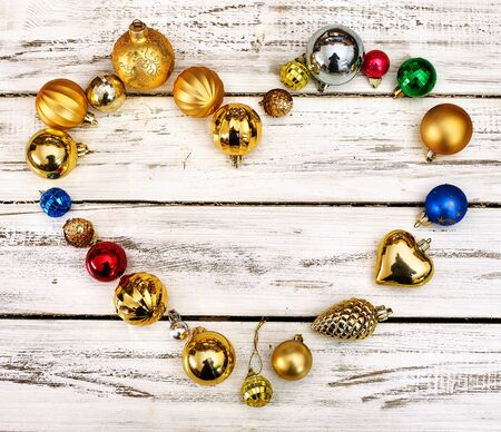 Christmas decorations scattered heart form design top view of Xmas balls ornaments on white wooden table. Square frame. Standard-Bild