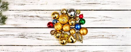 Christmas stack of Xmas balls decorations on white wooden table on horizontal long frame banner with copy space around. Standard-Bild