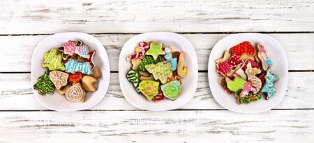 Christmas gingerbread cookies on three plates group by white wooden table . Top view long horizontal banner design frame with copy space top. Standard-Bild