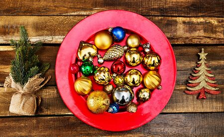 Christmas decorations design of Xmas balls ornaments on red plate with green tree on wooden boards. Horizontal frame