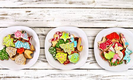 Christmas gingerbread cookies on three plates by white wooden table close up. Top view long horizontal banner design frame with copy space top.
