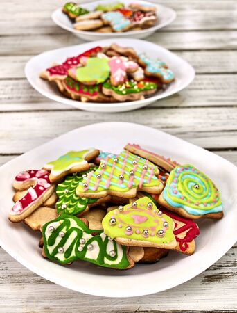 Christmas gingerbread cookies on three plates by white wooden table . Top view long vertical design frame.