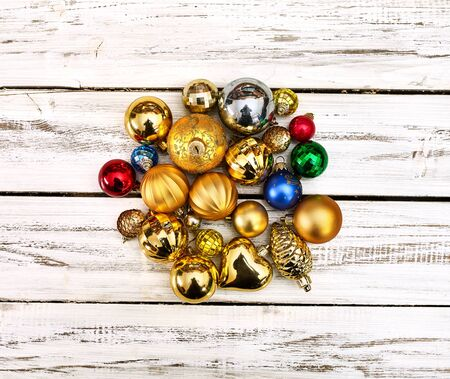 Christmas stack of Xmas balls decorations on white wooden boards on square frame with copy space around still life .