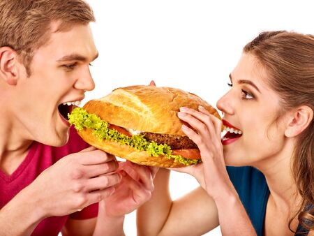 Couple eat fast food after self isolation. Women and man take junk food and commensality. Hamburger eating competition Standard-Bild