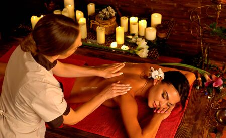 Shoulder and neck woman oil pressure massage by master acupressure therapy professiona with top view large group of candles in day spa. Standard-Bild
