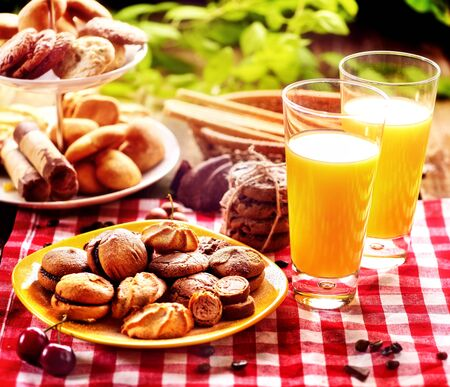 Chocolate oatmeal cookies and sand heart shape cake on plate table with fresh orange juice glass drink in farm style. Table setting breakfast on gingham tablecloth. Perfect product. Dessert in cafe.