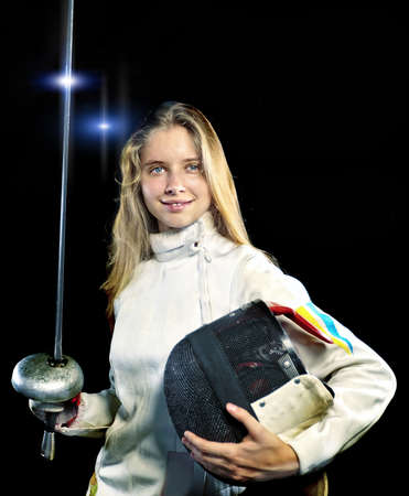 Fencing girl holding weapon and mask. Sport portrait of beautiful female fencer on black background with spark.