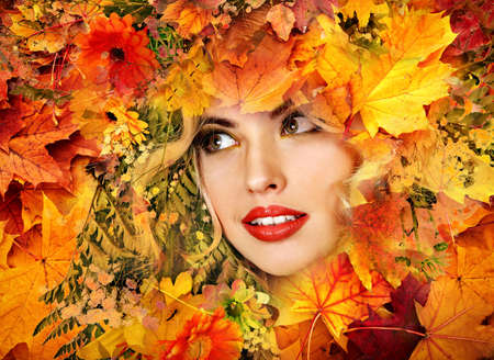 Autumn leaves background with beauty face of beautiful woman close. Fashion dream in red fall color outside. 版權商用圖片
