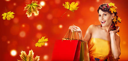 Autumn sale shopping bag banners maple leaves background with beautiful woman. Fashion dream in red fall color outside. 版權商用圖片