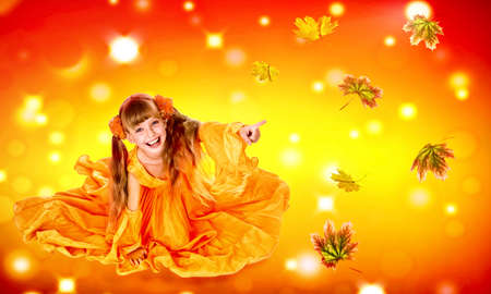 Autumn leaves background with child girl. Conceptual fashion dream in red fall color of september sun. Kid playing with leaves in fall.