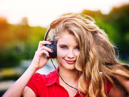 Woman with headphones listening summer music. She happy, smiling and looking at camera in park outdoor.