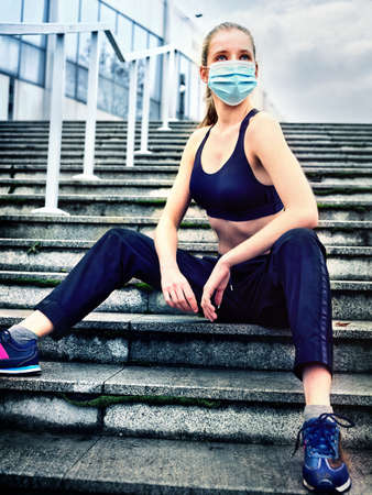 Running with fitness in medical mask. Sport of jogging woman during quarantine protection from coronavirus covid virus. Control and Prevention by training surgical masks.