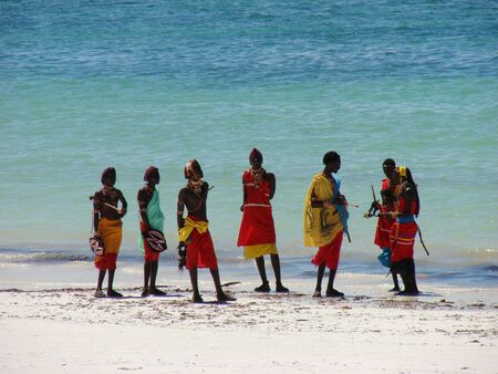 Diani Resort (30 km south of Mombasa), Kenya, Africa 02 May 2007 : Group of male Masai on a beautiful kenyan beach in traditional clothes. Amaizing colors - light sand blue sky and turquoise ocean.