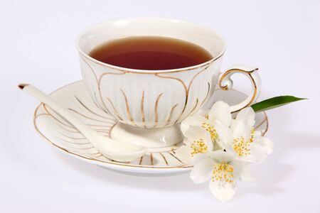 Cup of tea with jasmine flowers isolated on white. photo