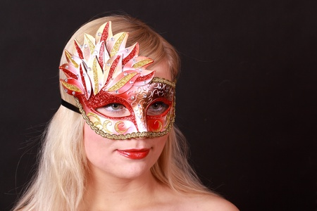 Face of young woman with carnival mask isolated on black photo