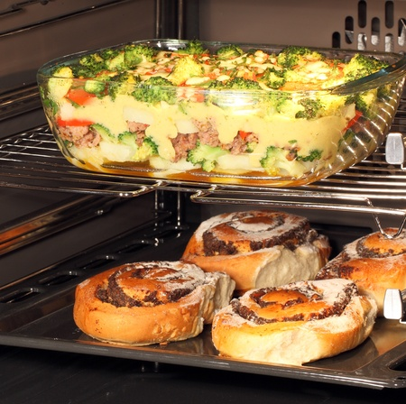 oven tray: Fresh baked poppy seed rolls and casserole dish with bechamel sauce in oven. Hot air allows the burning of different dishes simultaneously. Stock Photo