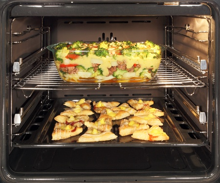 bakery oven: Fresh baked homemade cookies and casserole dish with bechamel sauce in oven. Hot air allows the burning of different dishes simultaneously.