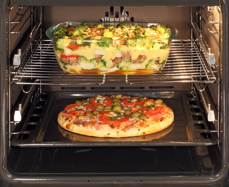 simultaneously: Baking pizza and casserole dish with bechamel sauce in oven. Hot air allows the burning of different dishes simultaneously.