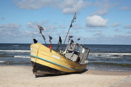 yellow boats: Fishing boat on Baltic Beach in Niechorze, Poland Stock Photo