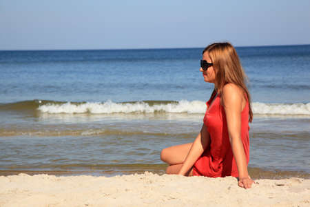 Young woman sitting on a sunny beach  Stock Photo - 10568925