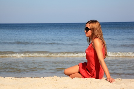 Young woman sitting on a sunny beach Stock Photo - 10568926