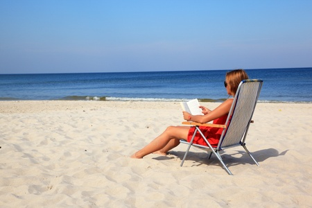 Young woman reading book on the sunny beach Stock Photo - 10569014