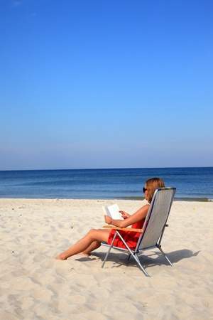Young woman reading book on the sunny beach Stock Photo - 10568993