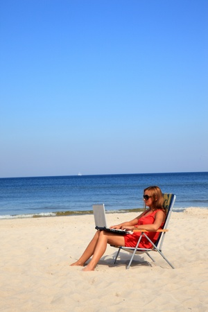Young woman with laptop is sitting on the sunny beach.  Stock Photo - 10568897