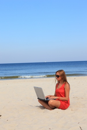 Young woman with laptop is sitting on the sunny beach.  photo