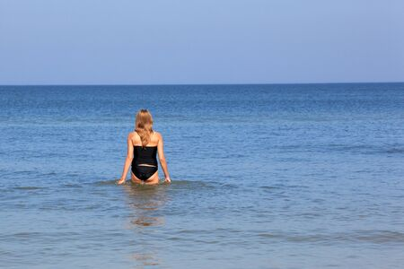 Beautiful young woman walking in the Baltic sea. Stock Photo - 10632746