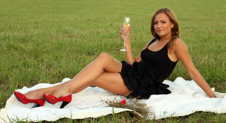 legs open: Girl drinking champagne in the park