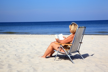 Mature woman reading a book at the beach photo
