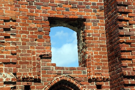 Blue sky in holes on old red brick wall photo