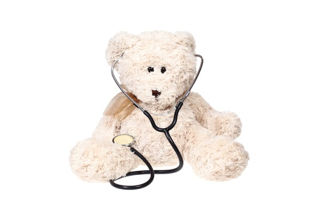 Teddy bear and stethoscope isolated on white photo