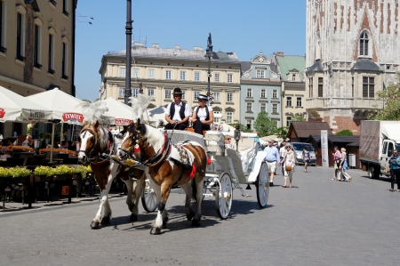 KRAKOW, POLAND - MAY 20: Horse-drawn carriage at City Square on May 20, 2012 in Krakow, Poland. Horse-drawn carriage tour of Krakow is a great attraction for tourists from around the world. Stock Photo - 13714409
