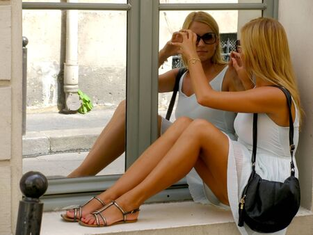 Young teen girl and her mirror image reflection in window  photo