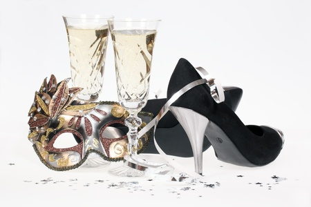 Masquerade mask, champagne and high heel shoes isolated on white background