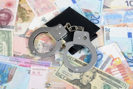 financial diversification: Currency from world with handcuffs and wallet Stock Photo