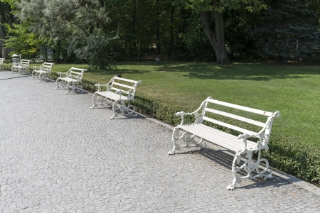White bench decorated with dog heads  Wilanow Park in Warsaw, Poland photo